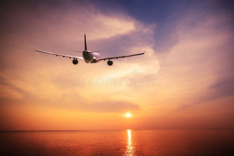 Flygplan som flyger över det fantastiska tropiska havet på solnedgången Thailand lopp arkivbilder