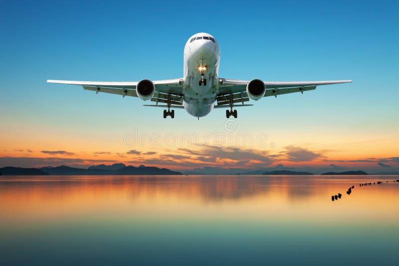 Flygplan som flyger över det tropiska havet på den härliga solnedgången eller soluppgång arkivfoton