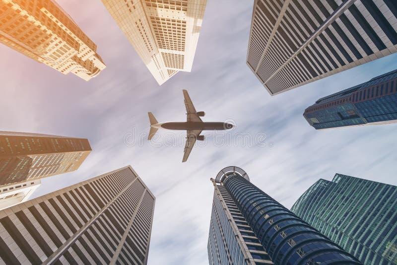 Flygplan som flyger över stadsaffärsbyggnader, höghusskyscrap royaltyfria bilder
