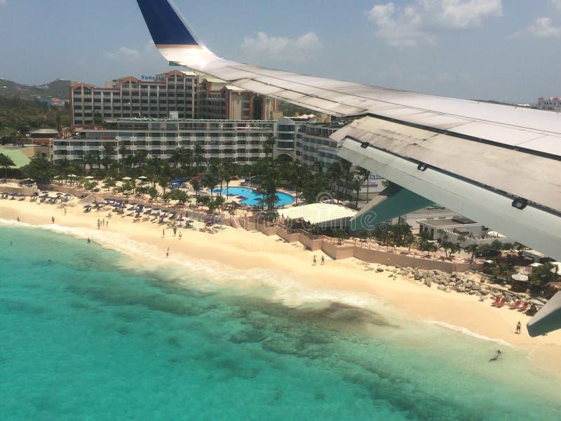 Flygplan som flyger över stranden för St Maarten royaltyfri fotografi