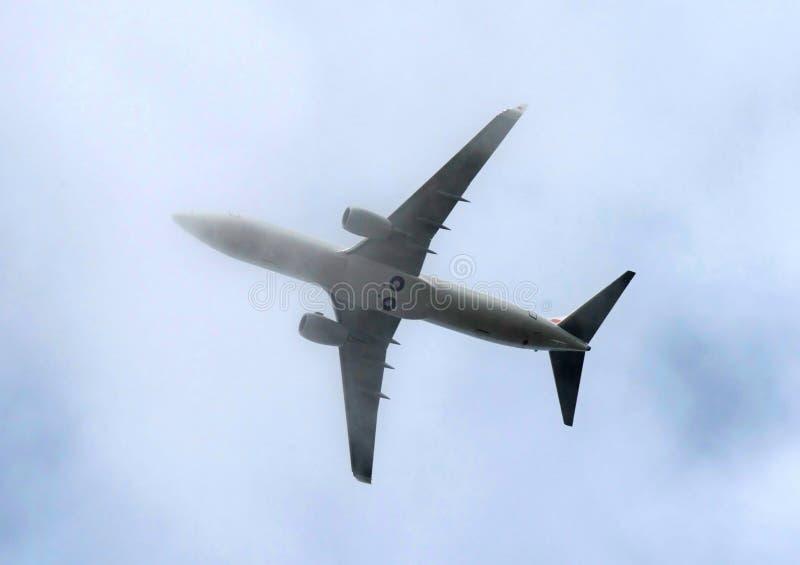 Flygplan som högt flyger till och med täta moln i blå himmel royaltyfria bilder