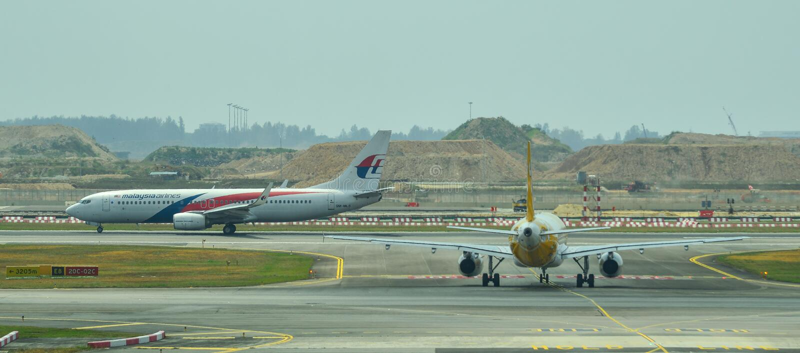 Flygplan som ?ker taxi p? landningsbana av den Changi flygplatsen royaltyfri fotografi