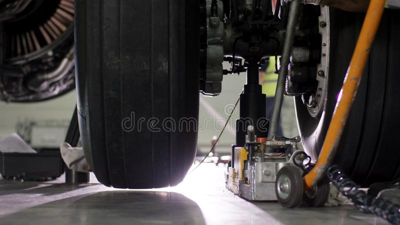 Flygplanbromsreparation Slut upp av den flygplanhjulet och axeln Enormt flygplandäck med axeln och landningkugghjulet av nivån arkivbild