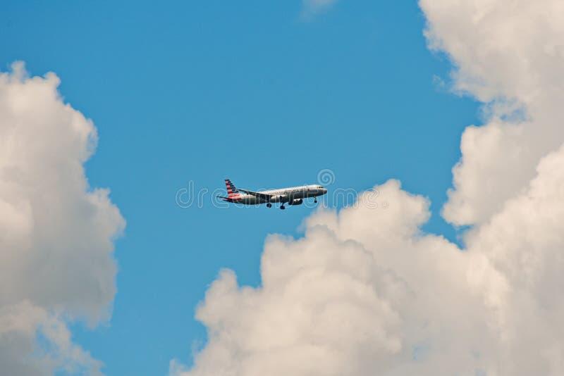 Flygplanet från American Airlines, landar på Orlando Airport på backround för molnig himmel arkivfoton