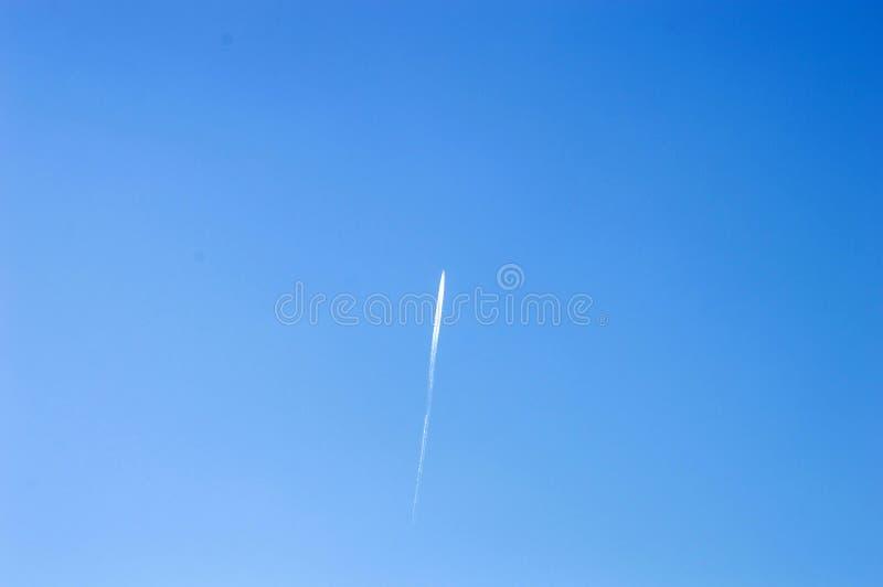 Flygplanet i himlen och klungan av lämnade moln, nivån i den blåa himlen och klungan av moln som det lämnar royaltyfria foton