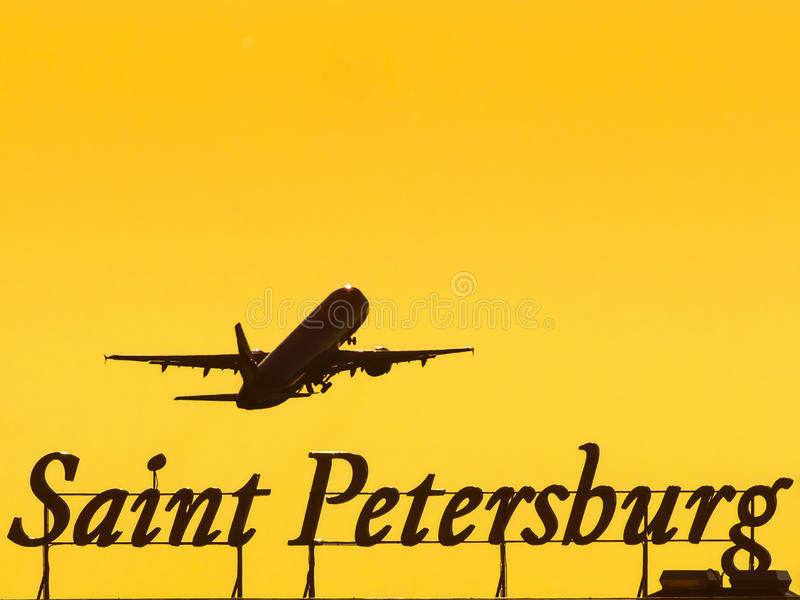 Flygplanet på start flyger ovanför inskriften av staden av St Petersburg på solnedgången royaltyfri bild