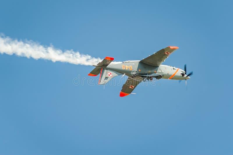 Flygplanet som utför på airshow och sidor bak a, röker i himlen Uppochnervänt flyg royaltyfria foton