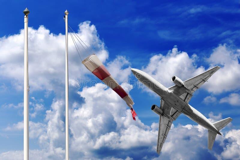 Flygplanet tar av i en härlig sommarhimmel med den röda och vita windsocken arkivbilder