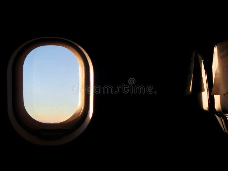 Flygplanfönstersolnedgång royaltyfri bild