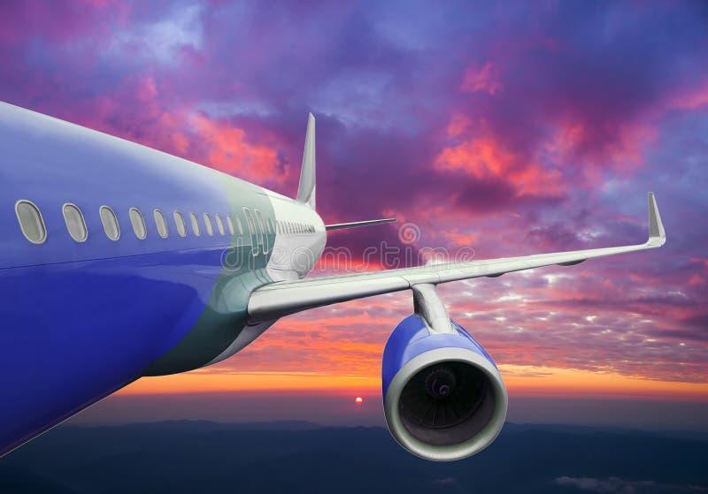 Flygplanflyg i de härliga solnedgångmolnen fotografering för bildbyråer