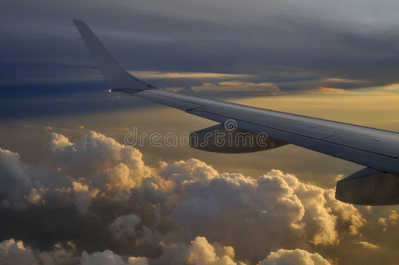 Flygplanflyg ovanför molnen mot en härlig solnedgång royaltyfria bilder