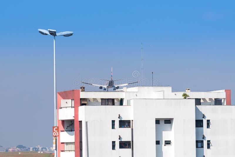 Flygplanflyg som är högert över byggnadstaköverkanten royaltyfria foton