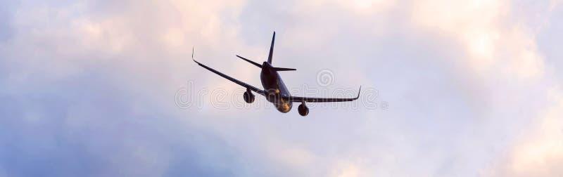 Flygplanflyg till och med en aftoncloudscapepanoramautsikt arkivfoto
