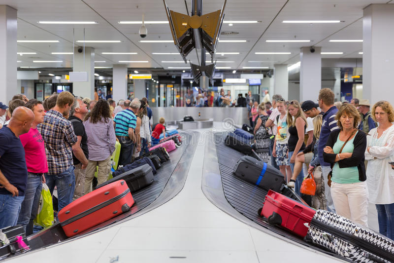 Flygplanhandelsresande som väntar på deras bagage på den Schiphol flygplatsen i Amsterdam, Nederländerna arkivbild