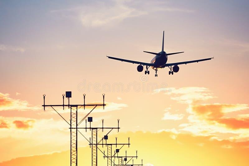 Flygplanlandning på solnedgången arkivfoton