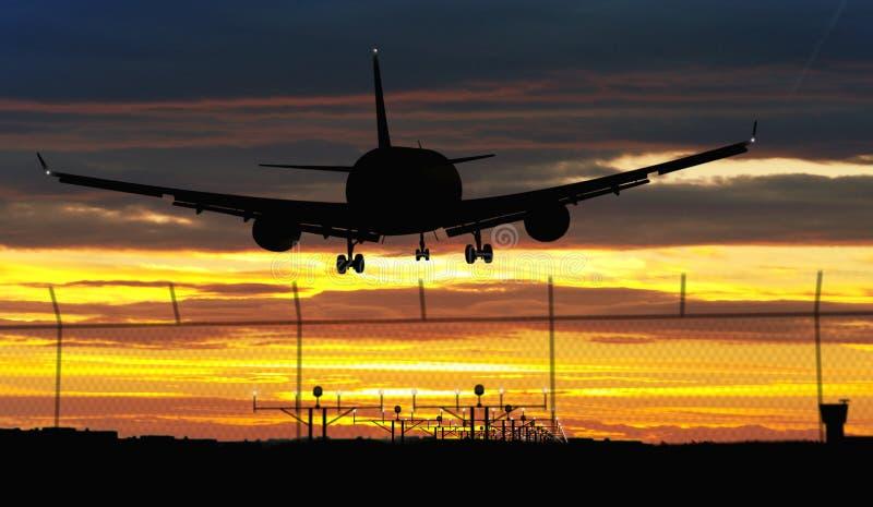 Flygplanlandning på solnedgånghimmel royaltyfri fotografi