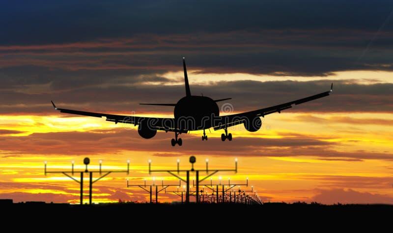 Flygplanlandning på solnedgånghimmel arkivfoto