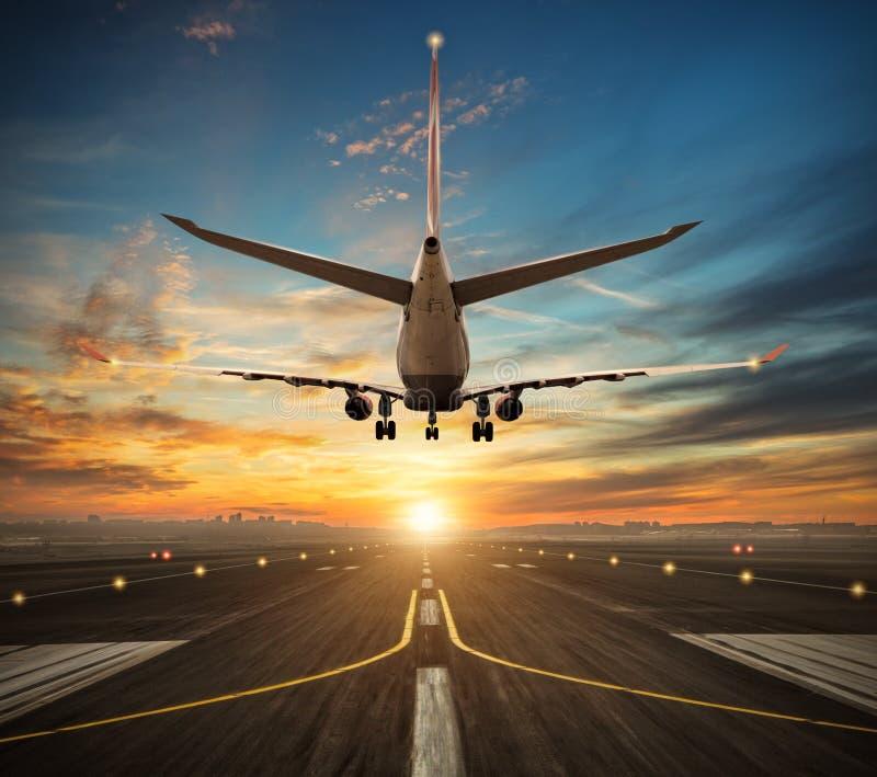 Flygplanlandning till flygplatslandningsbanan i solnedgångljus royaltyfri foto