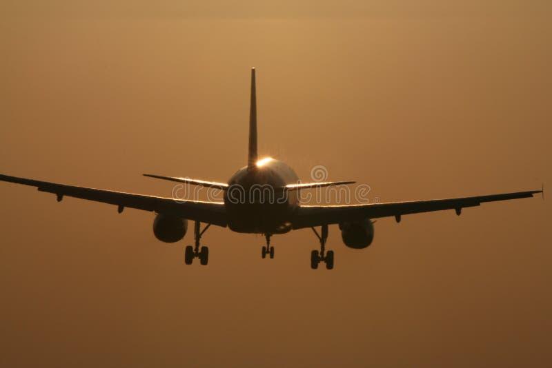 flygplanlandningsolnedgång royaltyfria foton