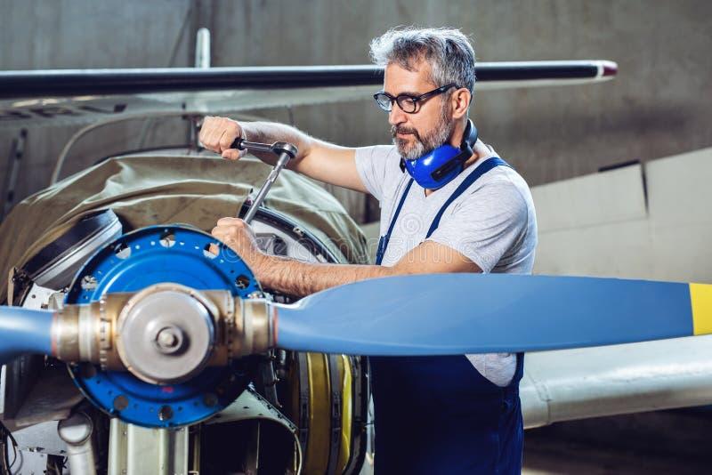 Flygplanmekanikern reparerar en flygplanmotor royaltyfria foton