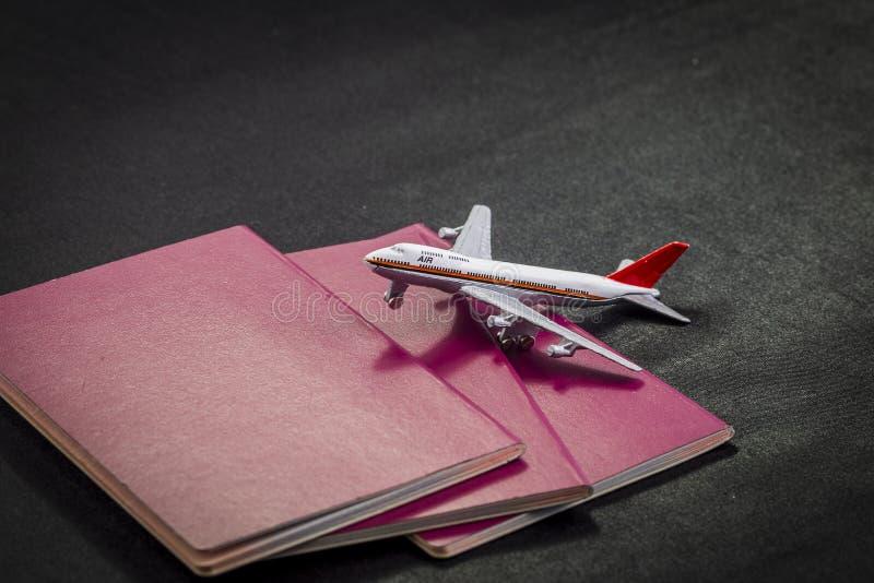 Flygplanmodell på den internationella pass, kreditkortar och resväskan på en svart bakgrund arkivfoton