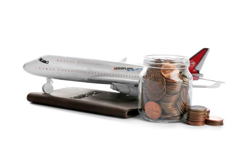Flygplanmodell, pass och krus med mynt på vit f?r r?knemaskinbegrepp f?r sedlar svart sparande f?r pengar fotografering för bildbyråer