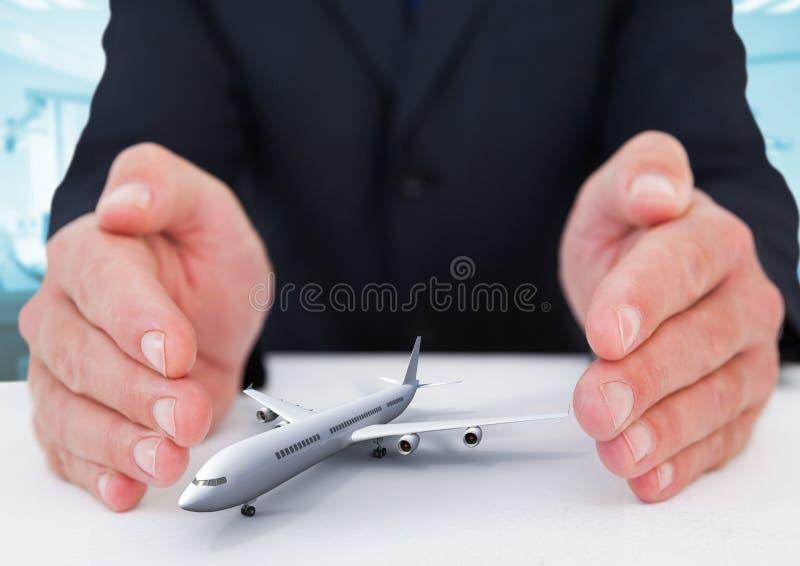 Flygplanmodell som omges av händer i gest av skydd arkivfoto