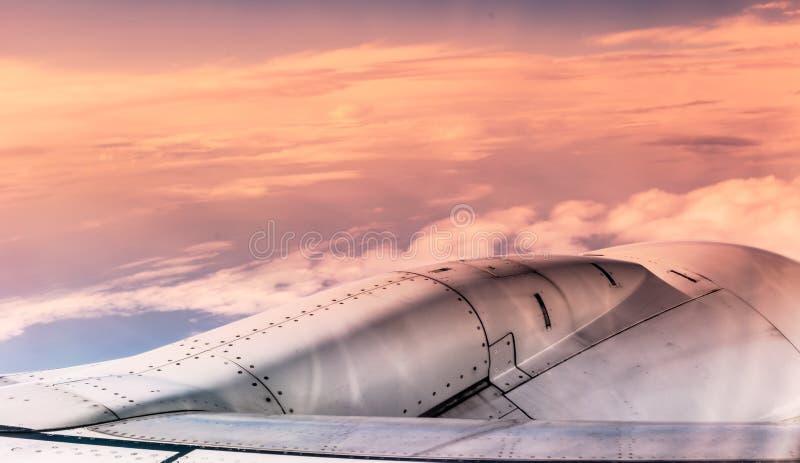 Flygplanmotor över solnedgångmolnsikt från flygplanfönster Fi royaltyfria foton