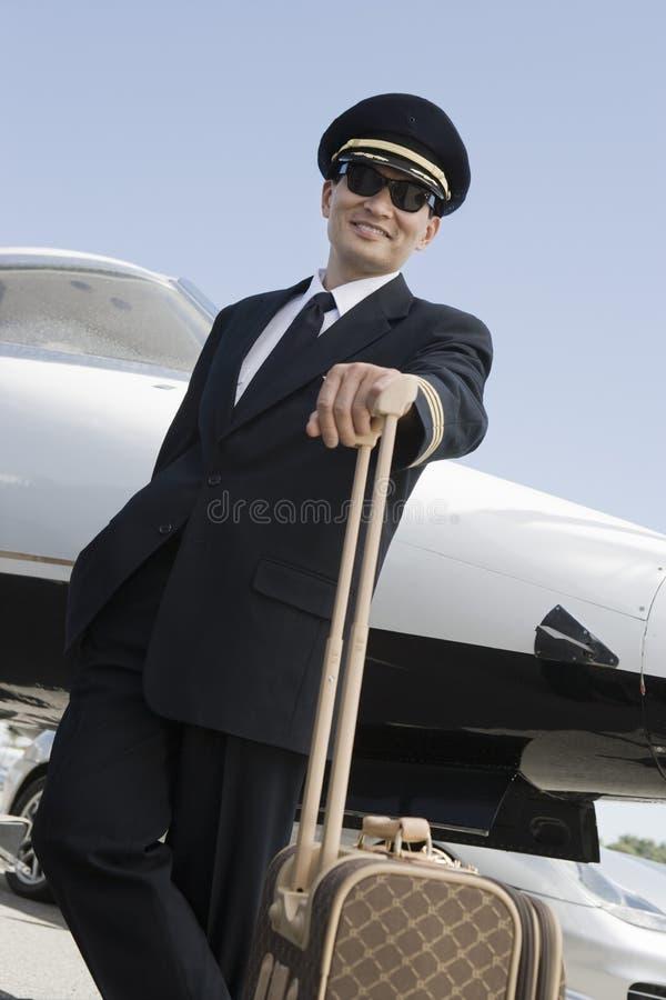 Flygplanpilot Standing With Luggage arkivfoto