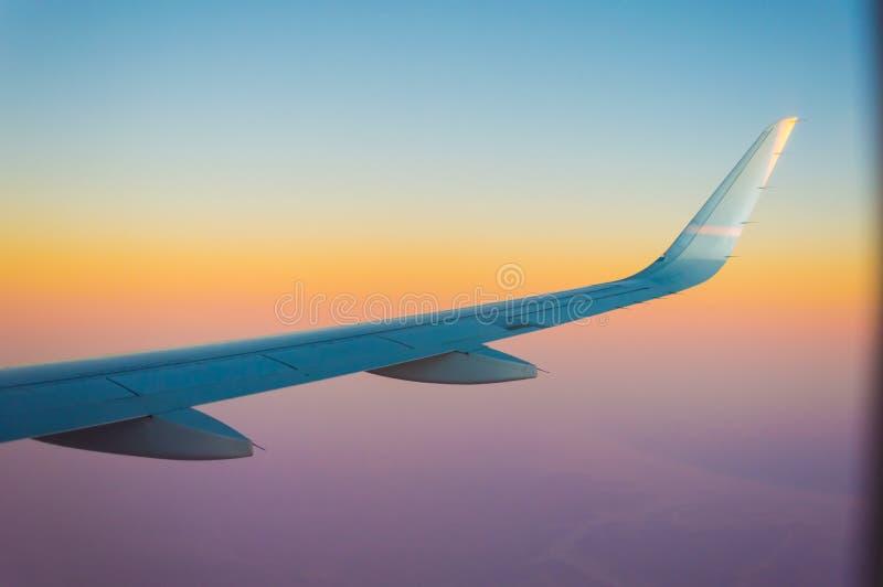 Flygplanvinge under en oerhörd solnedgång arkivbild