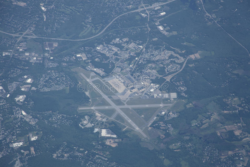 Flygplats och förorts- liggande från hög höjd royaltyfri bild
