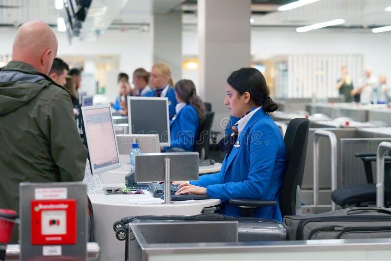 Flygplatsanställd registrerar bagaget Incheckning på flygplatsen royaltyfri bild