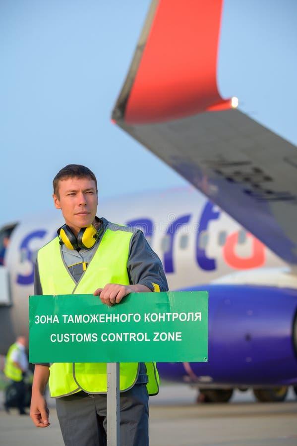 Flygplatsarbetaregenar undertecknar flygplanmanmannen arkivbilder