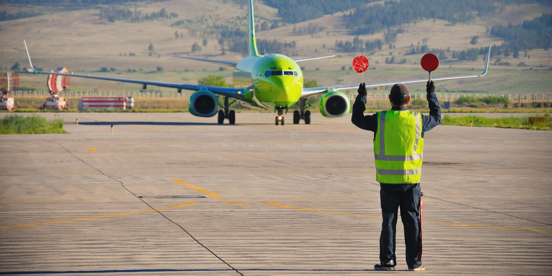 Flygplatsarbetarsignalerande royaltyfria bilder