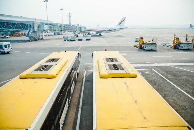 Flygplatsbuss bredvid landgång och flygplanet arkivbilder