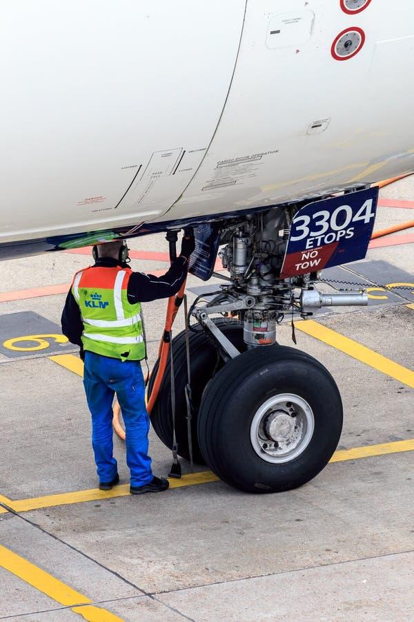 Flygplatsjordningsarbetare med flygplan royaltyfri foto