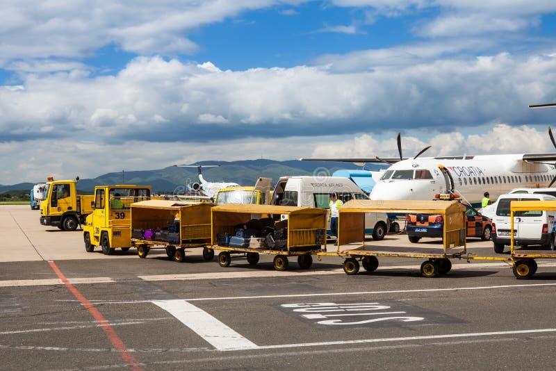 Flygplatslastbilar som behandlar bagage på den Zagreb flygplatsen royaltyfri bild