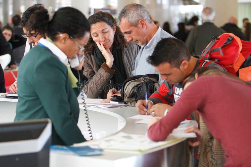 Flygplatspassagerare som fyller reklamationer under en viktig flygfördröjning royaltyfri bild