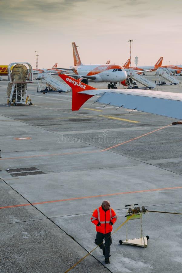 Flygplatspersonaler och rader av flygplan för Easyjet flygbuss A320 på Milan Malpensa flygplatsgrov asfaltbeläggning Trafikflygpl arkivbild