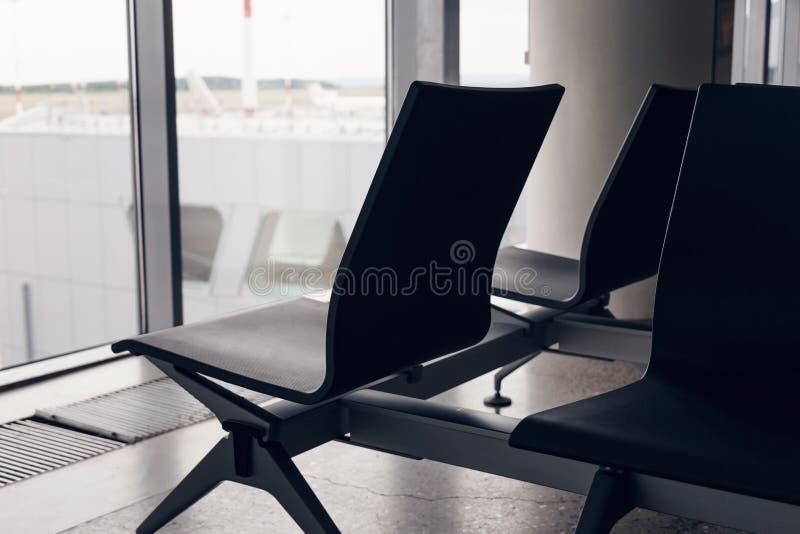 Flygplatsplacering Tomma bänkstolar i avvikelsekorridoren arkivbild