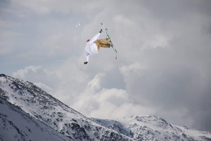 Flygskidåkare på snöig berg Den extrema sporten som är alpin skidar arkivfoton