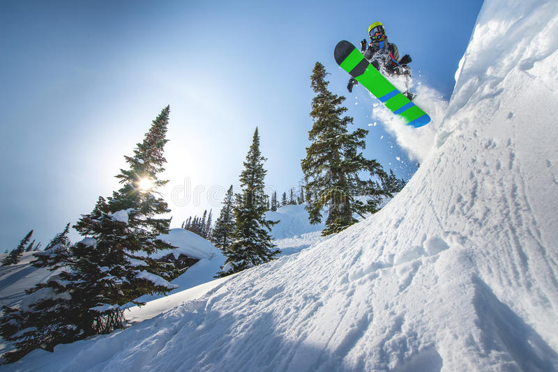 Flygsnowboarder i bergen royaltyfri foto