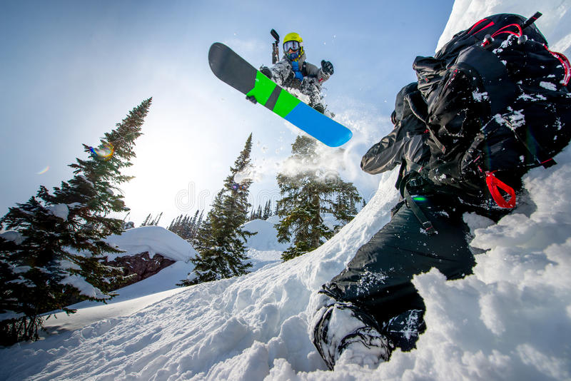 Flygsnowboarder i bergen arkivfoto