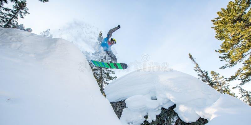 Flygsnowboarder i bergen arkivbilder