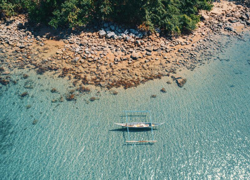 Flygtornvy över båten förankrad i bukten med klart och turkotiskt vatten på soldagen Båt i den tropiska lagunen Tropisk royaltyfri foto