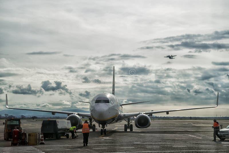Flygtrafikkontrollanten tar omsorg av att landa ett flygplan på flygplatsen, medan annan flyger i himlen fotografering för bildbyråer