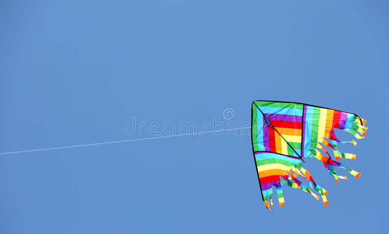 Flyies multicolores de la cometa en el cielo azul imágenes de archivo libres de regalías