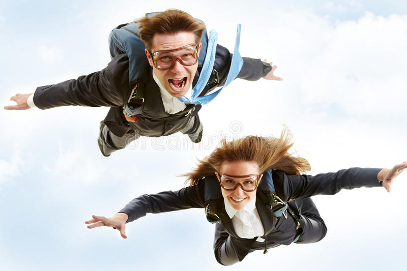 Flying. Conceptual image of young business partners flying with parachutes on their backs royalty free stock photos