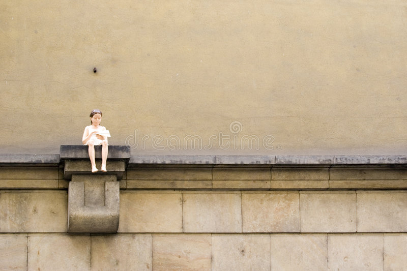 Flying. Statue of girl with a paper airplane sitting on a wall royalty free stock photo