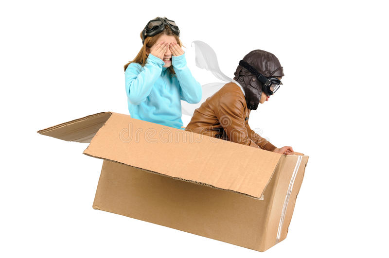 Flying. Youngcouple pilot flying a cardboard box isolated in white stock image
